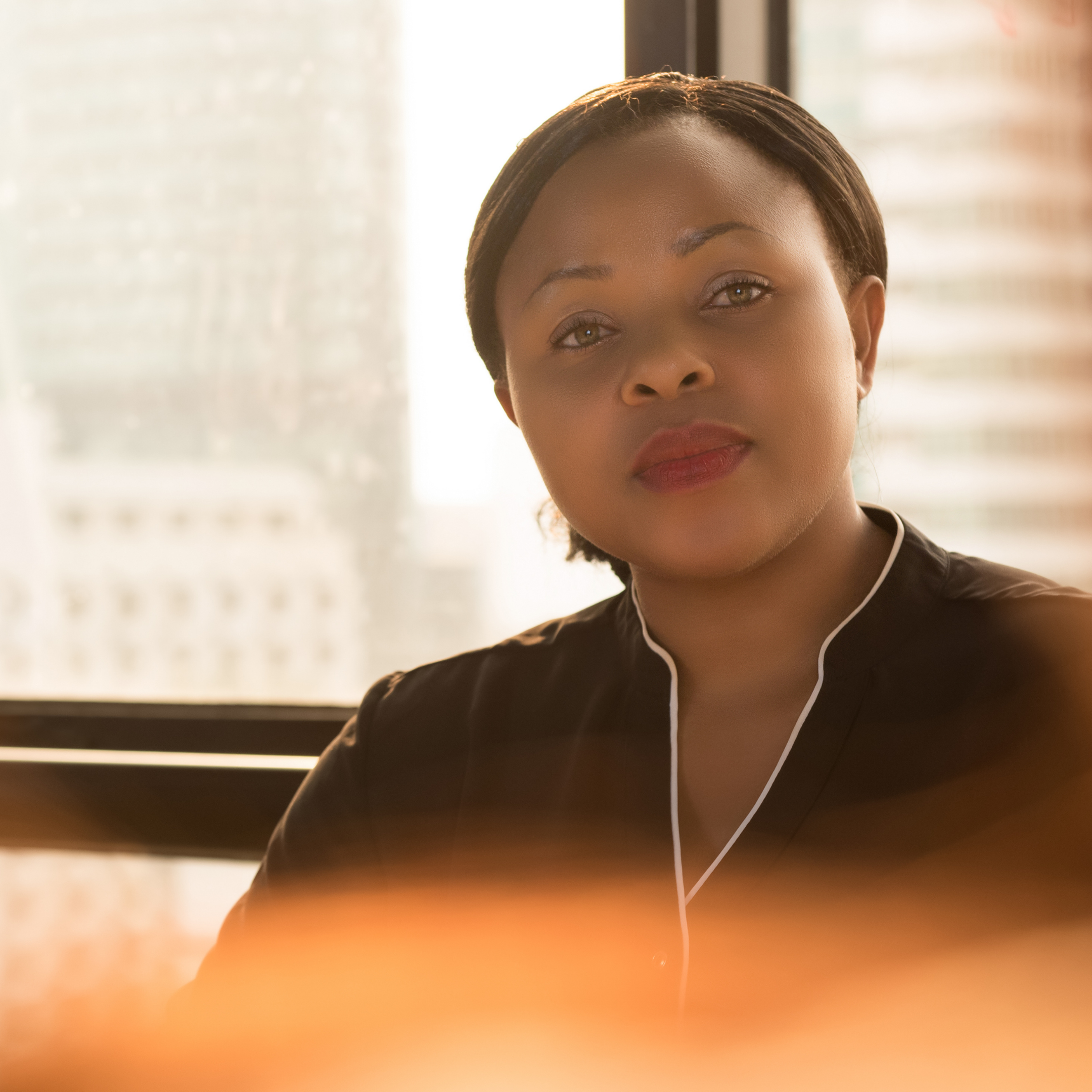 A beautiful black professional looking woman seemingly at work in a conference room.